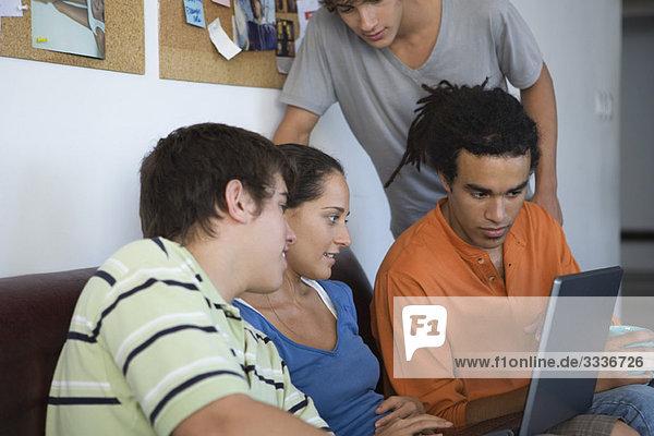 College-Studenten versammelt um Klassenkameraden mit Laptop-Computer