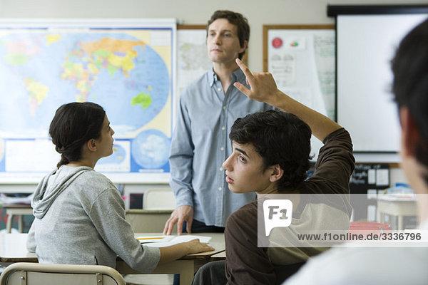 High school student raising hand in class  looking over shoulder