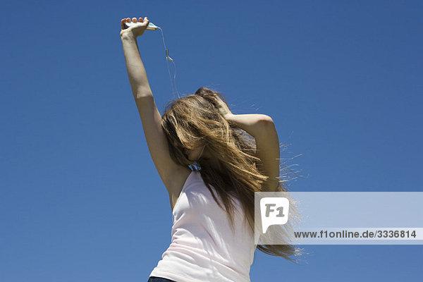 Junge Frau hört MP3-Player  tanzt im Freien