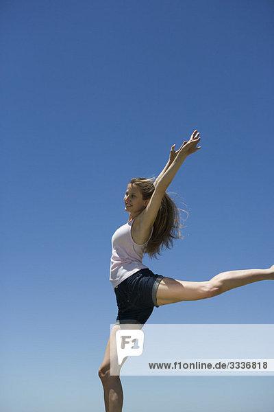 Junge Frau mit erhobenen Armen  auf einem Bein balancierend