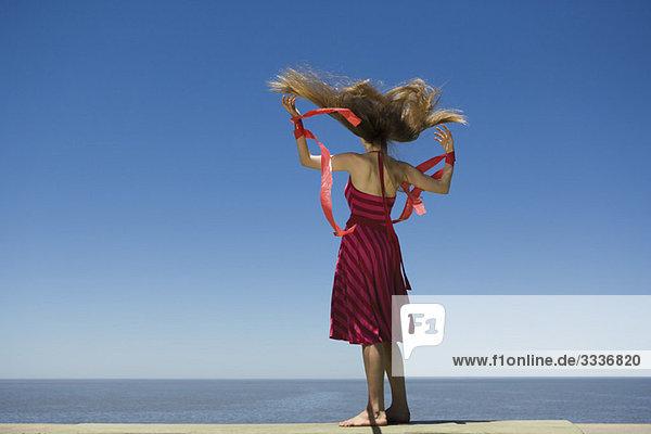 Junge Frau am Strand mit Blick auf die Aussicht  hält Luftschlangen im Wind