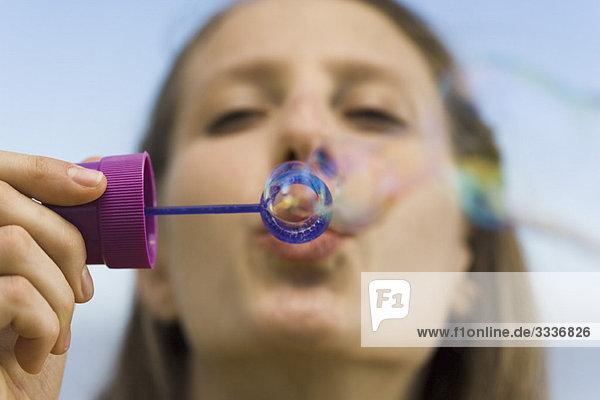 Junge Frau mit Blasenstab Blasen blasend