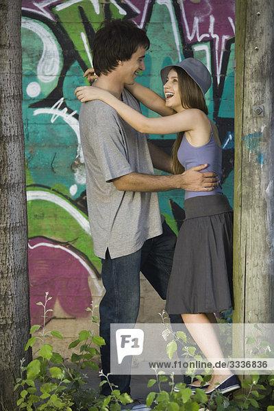 Junges Paar umarmt sich vor Graffiti-Wandgemälde
