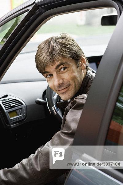 Mann im mittleren Erwachsenenalter  der ins Auto steigt und über die Schulter schaut  bevor er die Tür schließt.