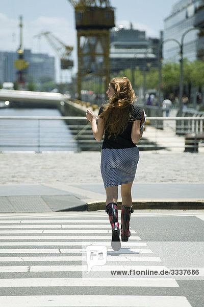 Young woman hurrying across crosswalk  rear view
