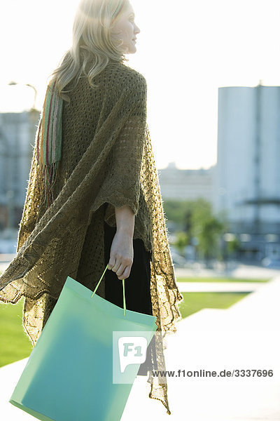 Frau mit Einkaufstasche  Spaziergang durch den Park