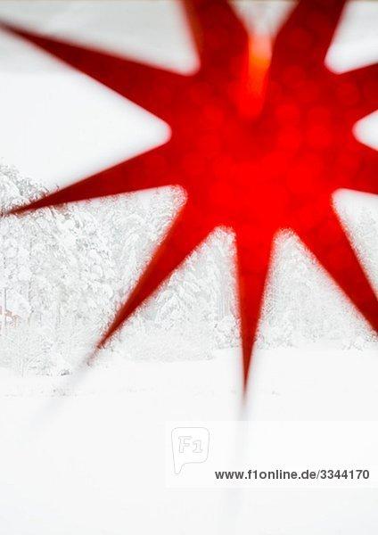 Ein red Advent Stern in einem Fenster,  Schweden.