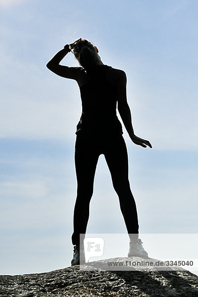 Young Frau macht stretching-Übungen gegen einen blauen Himmel  Schweden.