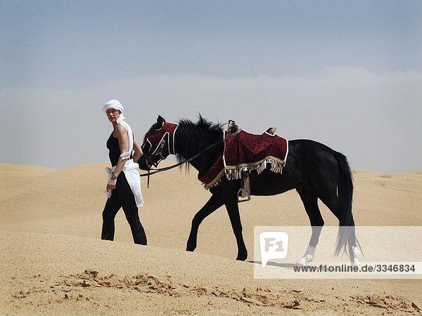 Frau mit einem Pferd in der Wüste  Tunesien.