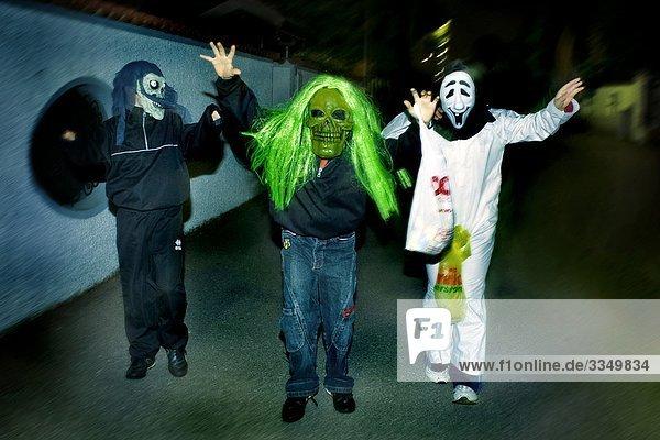 drei Personen verkleidet für Halloween zu Fuß auf der Straße