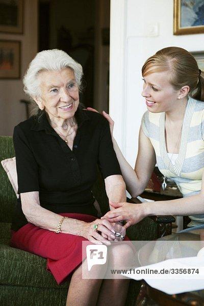 Zwei Frauen  die im Sessel sitzen und reden.
