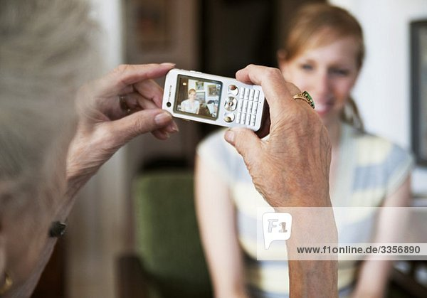 Ältere Frau beim Fotografieren einer jungen Frau mit Fotohandy