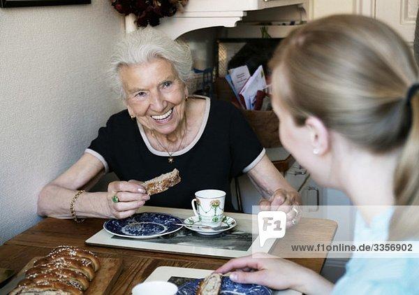 Zwei Frauen sitzen und essen Brötchen.