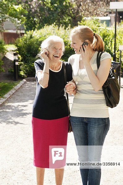 Zwei Frauen  die draußen auf dem Handy telefonieren.