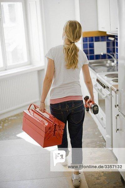 Frau mit Werkzeugkasten und Schraubendreher von hinten