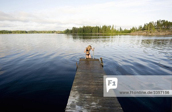 Woman entering water from pier