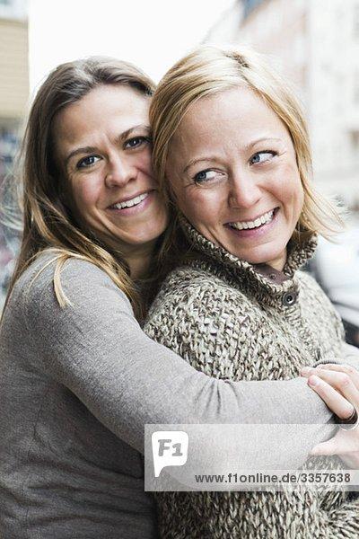 Freundinnen  die sich draußen umarmen Freundinnen, die sich draußen umarmen