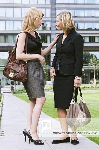 Zwei Geschäftsfrauen reden draußen.