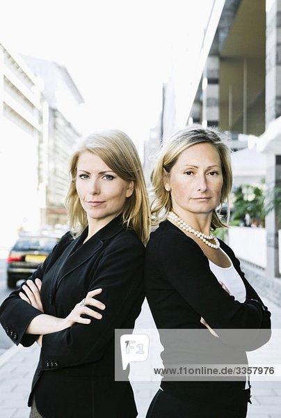 Zwei Geschäftsfrauen  die Rücken an Rücken stehen.