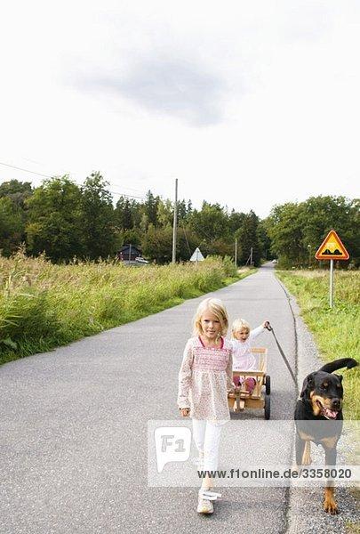 Kinder  die draußen mit dem Hund spazieren gehen