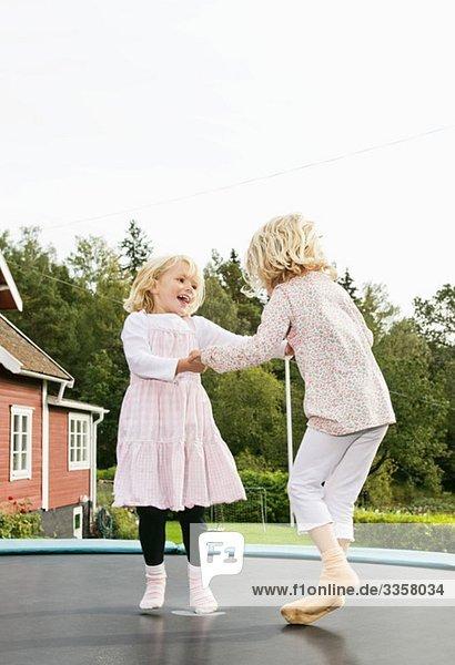 Zwei Schwestern springen auf Rebouncer