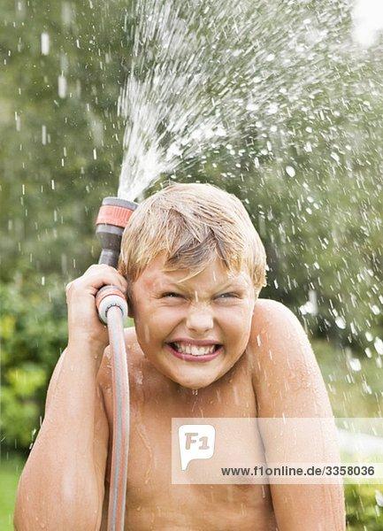 Junge hält Wasserschlauch Junge hält Wasserschlauch