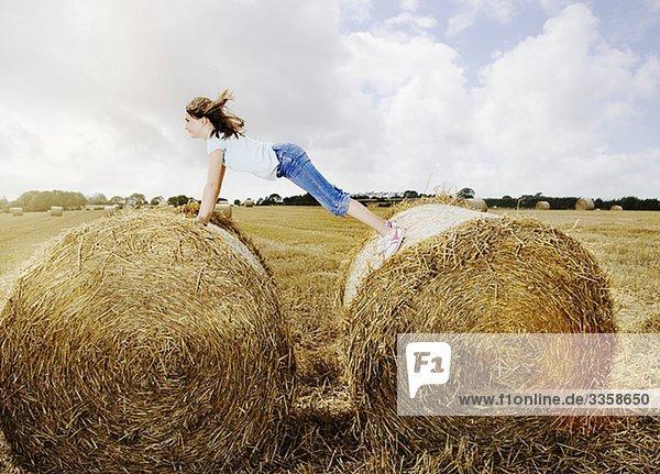 Mädchen balanciert zwischen zwei Strohballen