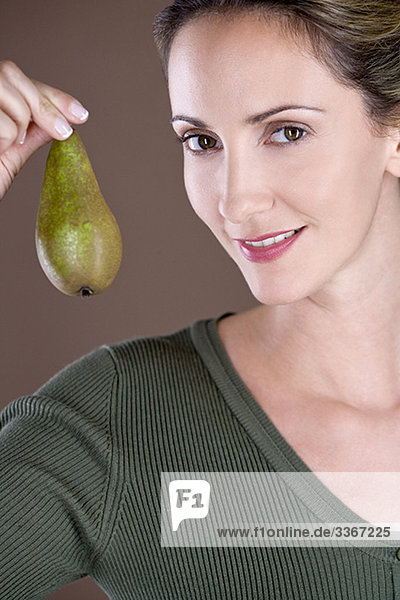 A mid adult woman holding a pear LV12886038