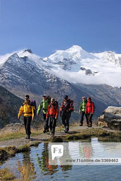 10870382  Walking  Hiking  group  cross ground  mountain lake  mountains  Alps  glacier  ice  moraine  canton Valais  walking  hiking  near Saas Fee  autumn  Switzerland  persons