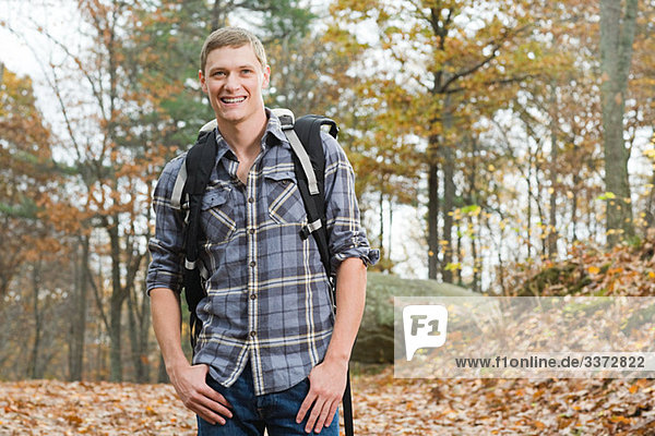 Young man in forest with backpack