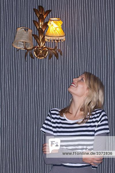 Junge Frau schaut zur Wandlampe hinauf