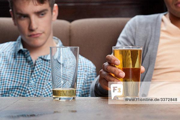 Junge Männer in der Bar mit Bier
