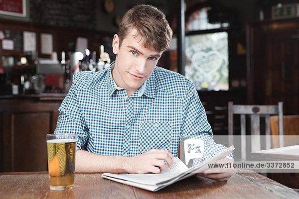Junger Mann in der Bar mit Zeitung und Bier