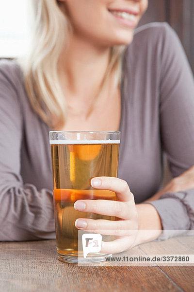 Junge Frau in der Bar mit einem Pint Bier