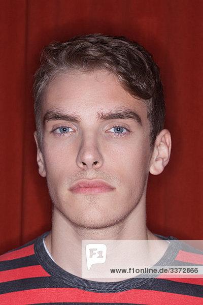 Porträt eines jungen Mannes vor rotem Hintergrund