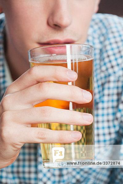 Junger Mann trinkt Bier  Nahaufnahme