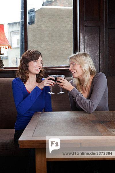 Zwei junge Frauen in der Bar beim Toasten mit Wein