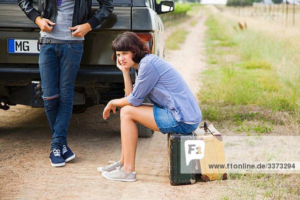 Paar wartet mit Geländewagen