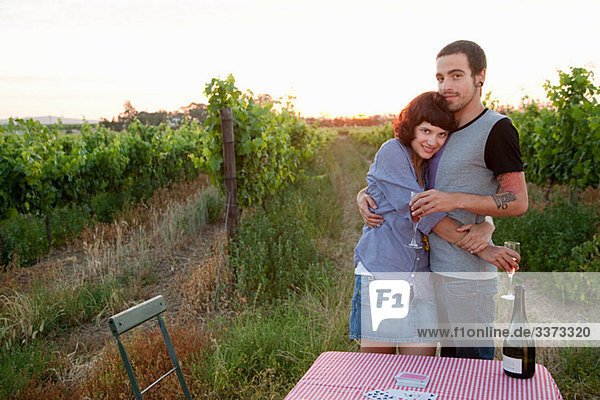 Paar in einem Feld mit Tisch und Wein