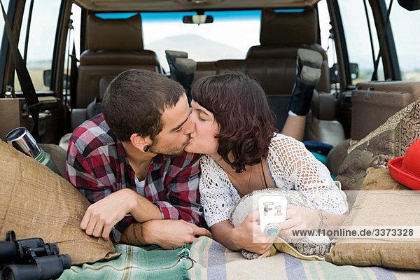 Junges Paar küsst sich im Rücken des Geländewagens
