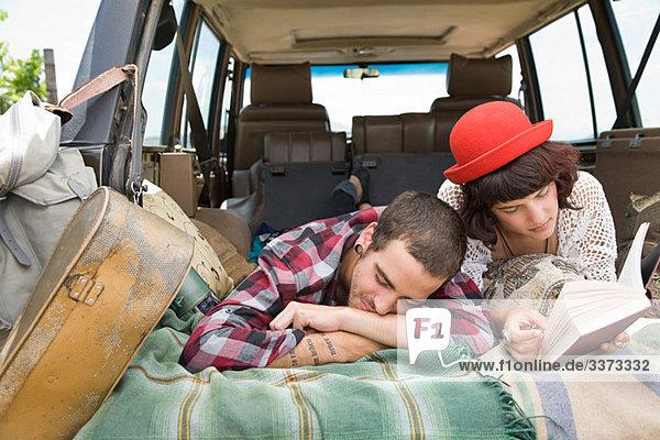 Pärchen liegend hinten im Geländewagen
