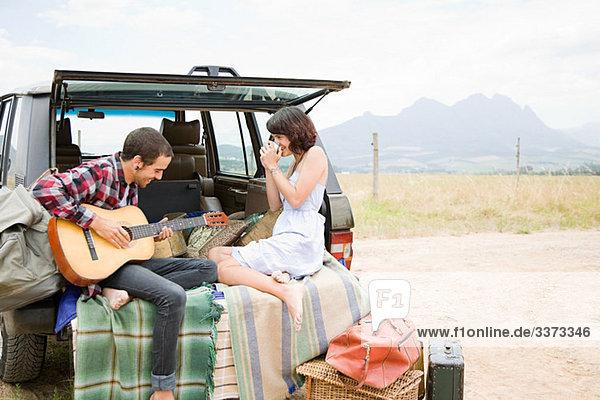 Mann spielt Gitarre für Freundin