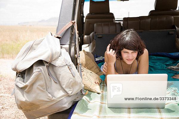 Frau mit Laptop im Fahrzeug