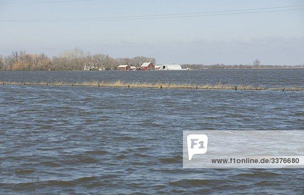 Frühling Fluten des Red River machen eine Insel mit einer Framyard  ländlichen Manitoba