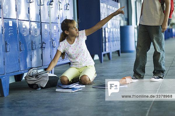Eine Schülerin sitzt auf dem Boden und zeigt wütend auf den Jungen  der über ihr steht.