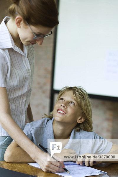 Der Schüler schaut auf den Lehrer lächelnd  während er seine Klassenarbeit bewertet.