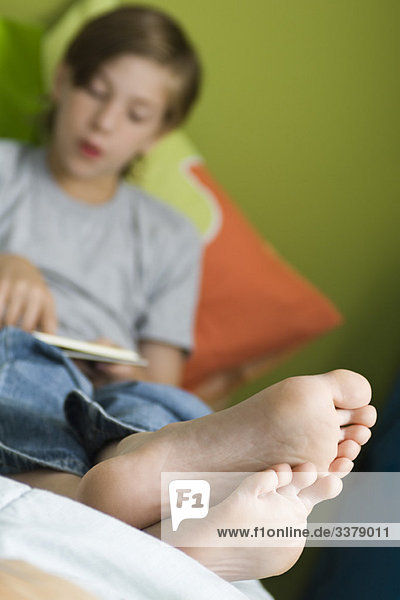 Boy Reclining With Feet Up Reading Book