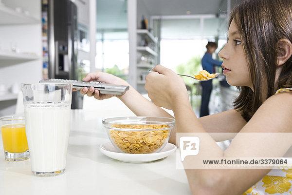 Mädchen wechseln beim Frühstück den Fernsehkanal