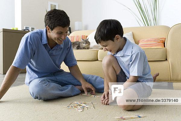 Vater und Sohn beim Spielen von Pick-Up-Stöcken
