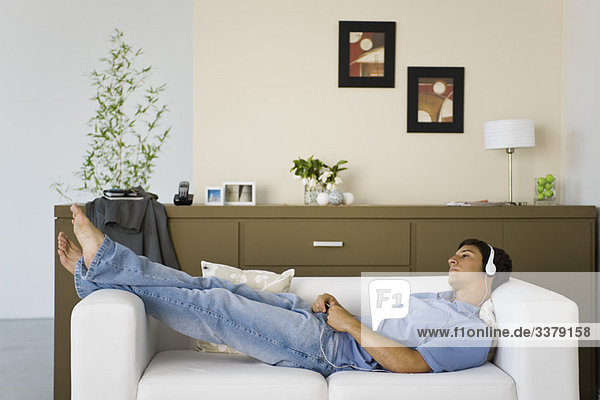 Junger Mann entspannt auf dem Sofa Musik hören mit Kopfhörern